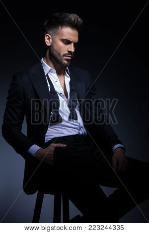 young man in tuxedo sitting with hand in pocket and looks down on dark background