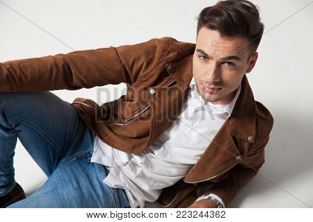 smiling young casual man lies down on grey studio background