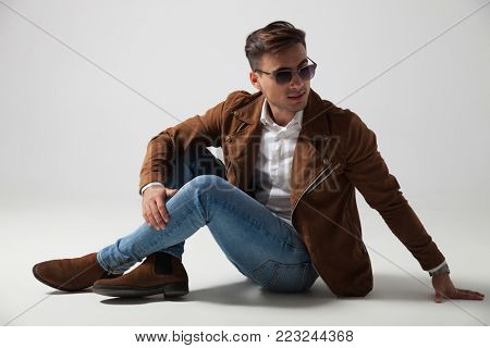 fashion man lying down and looks back over shoulder, wearing sunglasses and leather jacket on gry studio background