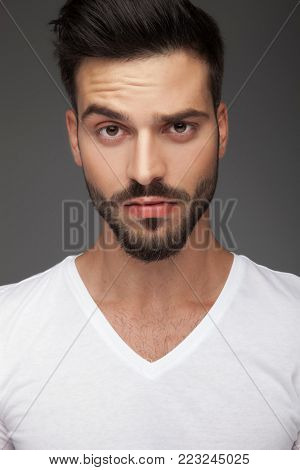 portrait of a cute man with raised eyebrow on grey background