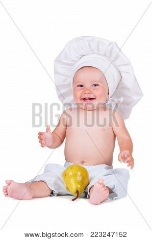 Cheerful little child with a pear in his hands in a chef suit on a white background