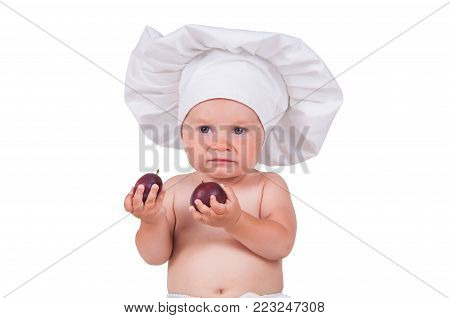A small child is eating plums in a chef suit on a white background