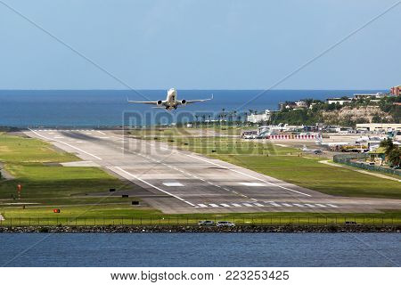 White passenger plane take-off from airport runaway. Aircraft flying above the ocean. Airplane front view.