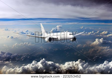 Civil wide-body plane in the sky. Aircraft flying on a high altitude above the storm clouds.