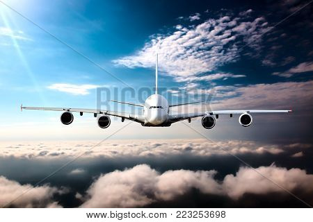 Civil wide-body plane in flight. Aircraft flying on a high altitude above the clouds. Airplane front view.