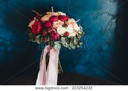 Isolated shot of beautiful colourful roses ties in bouquete with ribbon. Red and white flowers. Wedding`s bouquete. Decoration, celebration, bride, wedding