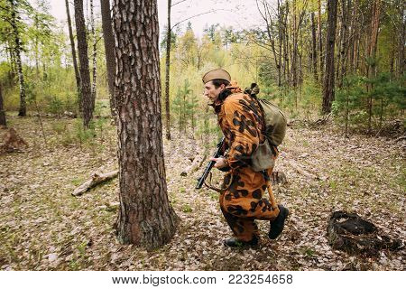 Pribor, Belarus - April 24, 2016: Re-enactor Dressed As Soviet Russian Red Army Infantry Soldier Of World War II Running In Attack With Submachine Gun In Forest At Spring Season.