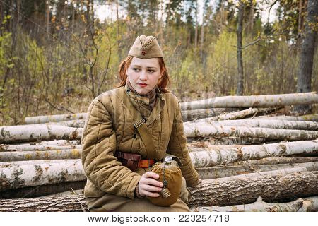 Pribor, Belarus - April 23, 2016: Young Woman Re-enactor Dressed As Russian Soviet Infantry Soldier Of World War II Sitting On Wooden Logs, And Drinks Water From A Flask In Forest