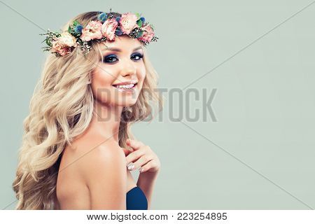Spring Woman with Blonde Curly Hair and Rose Flowers and Green Leaves in her Hair. Cute Model Girl with Blonde Wavy Hairstyle and Healthy Skin on Banner Background