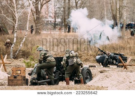 Gomel, Belarus - November 26, 2016: Re-enactors Dressed As German Soldiers In WWII Load A Cannon Shells At Firing Position. Celebration Of 73rd Anniversary Of Liberation Of Gomel From Nazi Invaders