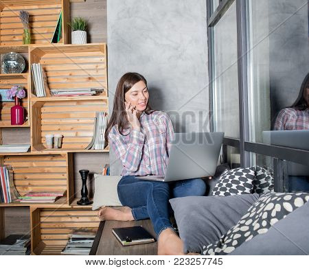 Woman talking with friend via mobile phone while sitting with net-book in home on windowsill. Female web site creator having cell telephone conversation during distance work on laptop computer