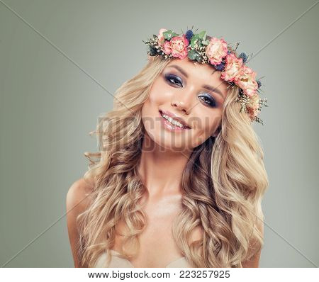 Smiling Blonde Woman Fashion Model in Rose Flowers Wreath. Beautiful Model with Blonde Curly Hairstyle