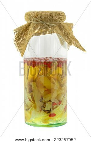 Chinese medical liquor in glass jar. Infused alcohol with herbs, isolated on white - Licorice, Radix Ginseng, Goji berry, Red sage, Solomon's Seal Rhizome, Female ginseng, Astragalus, Szechuan lovage