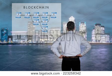 Blockchain schematic on glass panel with senior technology executive looking at the chart with London in background