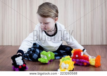 little boy in pajamas playing cars, sculpts from constructor velcro.