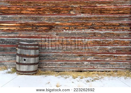 Old whiskey barrel set against a rustic log cabin wall in the snow
