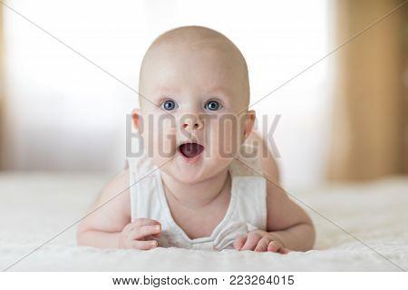 Cute baby wearing lying on belly in nursery room