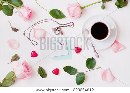 St Valentines day background. Cup of coffee, peach roses, blank card, owl shaped clock, heart shaped candies on white background. St Valentines day background. Flat lay, top view of St Valentines day still life