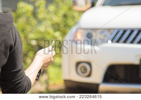woman hand holding the remote control to lock the car door.car security anti thief alarm system