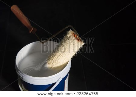 a bucket of paint and a brush roller.opened can of white paint and a roller on black background.
