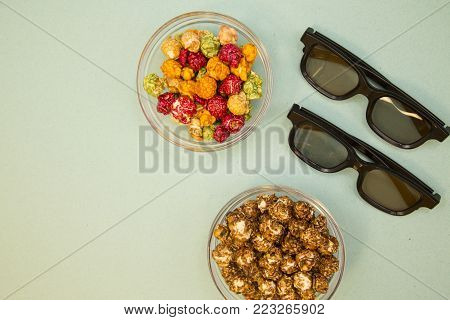 Weekend, Leisure, Lifestyle Concept. Ready to have fun 3d glasses and sweet colorful caramel popcorn on a light blue background, flat lay
