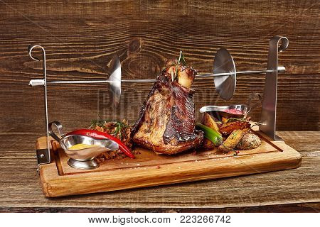 Roasted pork knuckle eisbein with braised boiled cabbage, potatoes and mustard on wooden cutting board. Wooden background. Original food in the restaurant