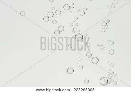 Many small gray bubbles flowing in a glass.