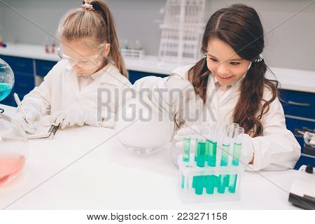 Two little kids in lab coat learning chemistry in school laboratory. Studying ingredients for experiments . Young scientists in protective glasses making experiment in lab or chemical cabinet