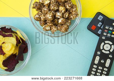 Weekend, Leisure, Lifestyle Concept. Weekend with family, two remote controls, sweet caramel popcorn and beetroot chips on a light blue and yellow background, flat lay