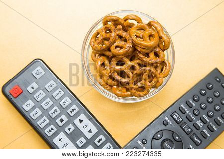 Weekend, Leisure, Hobby Concept. Weekend with movies, two remote controls and pretzels on a light orange background, flat lay