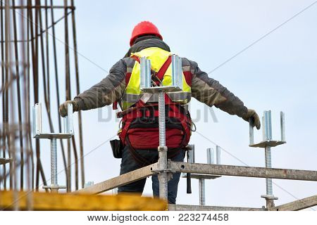 Climber with safety belt and red helmet on construction site over blue sky
