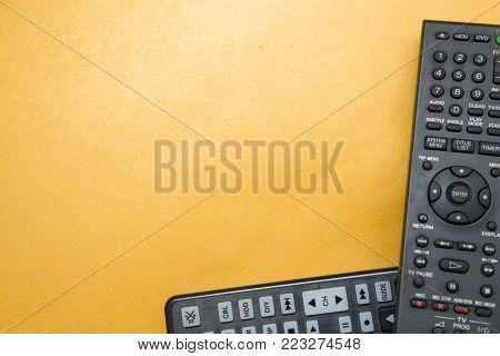 Weekend, Leisure, Hobby Concept. Weekend with movies, two remote controls on a light orange background with copy space, flat lay