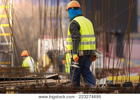 Builder in orange helmet at the construction site transfers armature