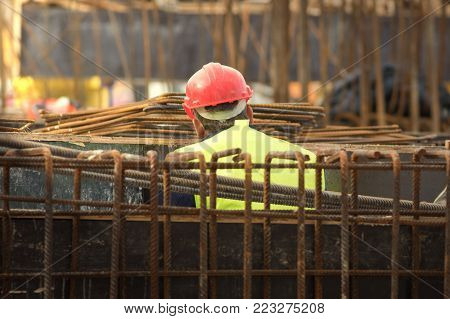 Worker with red helmeth behind the armature