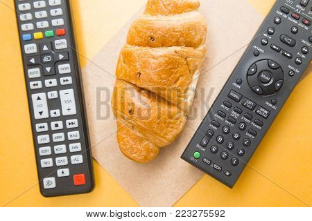 Weekend, Leisure, Hobby Concept. Weekend with movies, a remote control and a fresh croissant on a light orange background, flat lay