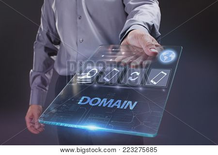 The concept of business, technology, the Internet and the network. A young entrepreneur working on a virtual screen of the future and sees the inscription: Domain