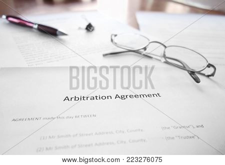 An Arbitration Agreement document on a desk with glasses and pen