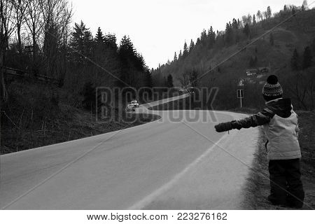 The boy travels hitchhiking in the mountains in fall or winter