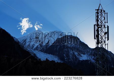 Sun rays and cellular transmitter in the sky over the Himalayas, Annapurna 2 in the Manang area