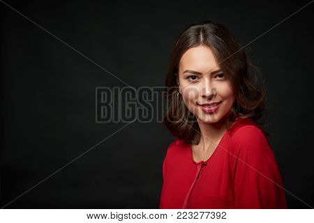 Closeup portrait of beautiful brunette woman in red shirt and wavy hair, over dark background