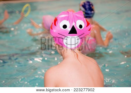 Lonely frustrated little girl with cute swimming cap sitting turned back on the swimming pool and looking children play. Close up.