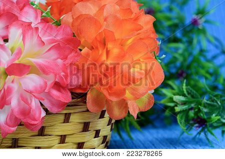 Bouquet of Artificial flower rose peony red white yellow and orange bright color made of synthetic fabric and plastic. Flowers lie in a wooden basket on table on light blue fabric. Objects close up.