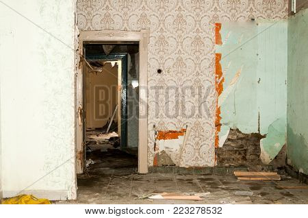 War damage. Remains of abandoned damaged and destroyed house interior by grenade shelling with collapsed roof and wall in the war zone selective focus