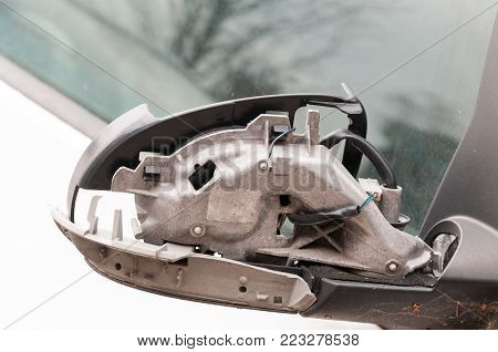 Damaged car. Damaged and broken rear-view mirror on the door on the car closeup