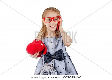 A small fashionist in red glasses is talking on the phone. A girl in the image of a businesswoman. Isolated on white background.