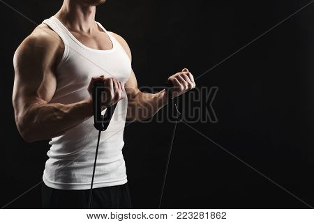 Sporty muscular man exercising with elastic expander at black studio background, low key, copy space
