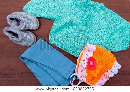 Baby clothes, booties and soother on wooden background. Kit for newborns