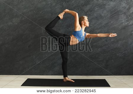 Fitness, woman training yoga in std bow pose in gym at grey background, copy space. Young slim girl making exercise.