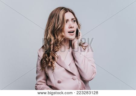 Surprised and indignant shocked girl talking on the phone, looking away on a white background, copy space