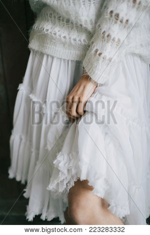 Girl in white ruffle skirt with flounces. Close-up. Artwork